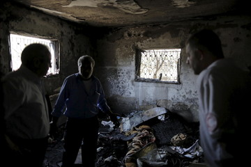 Palestinians inspect a house which was set on fire in a suspected attack by Jewish extremists in Duma village near Nablus
