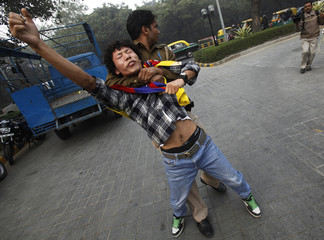 Police detain a Tibetan exile during a protest outside the hotel where China's Ma Xiaotian is staying, in New Delhi