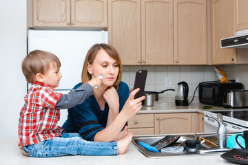 White Caucasian young woman mother housewife taking pictures selfie in kitchen, her child son boy playing and drawing on her cheek with marker, crazy parent life, funny kid moment