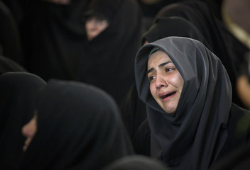 A woman cries during a funeral for recently found remains of an unknown soldier from the 1980-88 Iran-Iraq war in Tehran