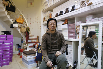 Renato Gu poses for a portrait inside his women's shoe and accessory shop in Rome