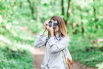 Young woman taking a photograph in the nature