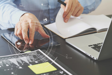 close up of businessman working with smart phone and digital tablet and laptop computer  on wooden desk in modern office with virtual icon diagram