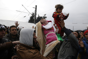 Migrants and refugees hold children during a protest at a makeshift camp at the Greek-Macedonian border near the village of Idomeni