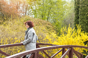 Pretty young red head woman on the bridge in spring park. Green trees and forsythia blossoms background.