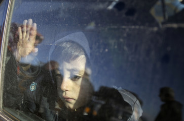 Palestinian boy, hoping to cross into Egypt with his family, looks out a car window as he waits at the Rafah crossing between Egypt and the southern Gaza Strip