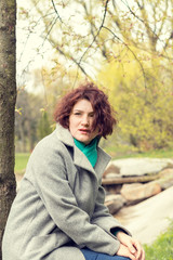 Pretty young red head woman sitting close to the tree in spring park. Spring trees background.