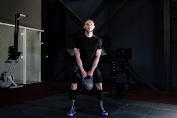 Young bearded man in sportswear working out with kettle bell at gym. Kettlebell training in gym