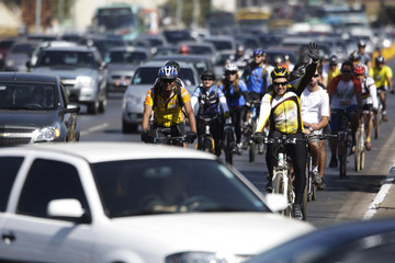 People who switched from using cars to bicycles in conjunction to World Car Free Day, wave on the streets of Brasilia