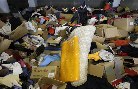 A boy searches for clothes to fit which were donated by people at a Red Cross office in Otsuchi