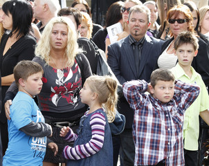 Family and friends watch following the funeral of slain technician Denis Blanchette in Montreal
