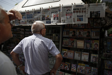 People read newspaper headlines on the results of the local and European Parliament elections at a kiosk in Athens