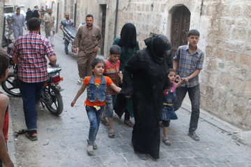 Women and children flee after an airstrike on Aleppo's rebel held Kadi Askar area
