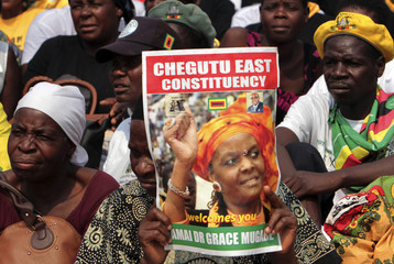 A supporter of Zimbabwe's First Lady Grace Mugabe holds a poster of her as she addresses her maiden political rally in Chinhoyi
