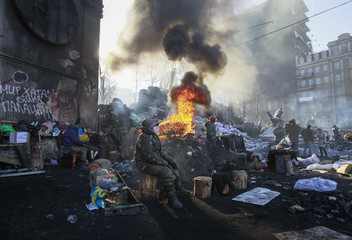 Anti-government protesters rest near an open fire, as temperatures reach minus 20 degrees Celsius at barricade near Independence Square in Kiev