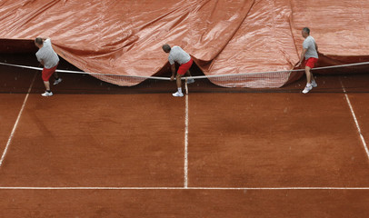 Workers cover Court One as rain interrupts a men's singles match between Tommy Robredo of Spain and John Isner of the U.S. at the French Open tennis tournament at the Roland Garros stadium in Paris