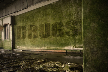 text drugs on the dirty wall in an abandoned ruined house