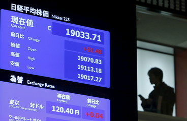 A man stands next to a stock quotation board displaying Japan's Nikkei average after a ceremony marking the end of trading in 2015 at the Tokyo Stock Exchange in Tokyo