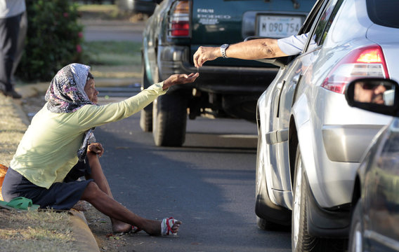 A man gives money to a woman begging on a street in Managua