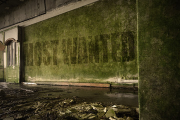 text most wanted on the dirty wall in an abandoned ruined house