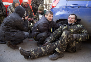 Anti-government protesters are injured during clashes with Interior Ministry members sit on the ground in Kiev
