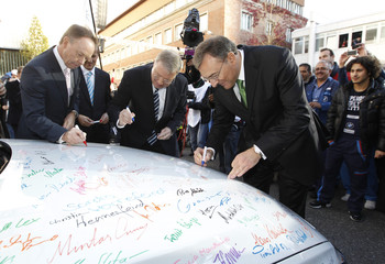 CEO of German luxury carmaker BMW Reithofer and a board member sign BMW 320d sedan during world premiere of company's new 3 series in Munich