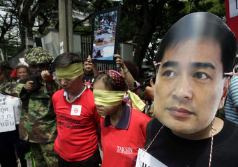 An anti-government protester wears a mask of Thai PM Abhisit as other people put on a skit mocking the recent anti-government protests, outside the U.S. embassy in Bangkok