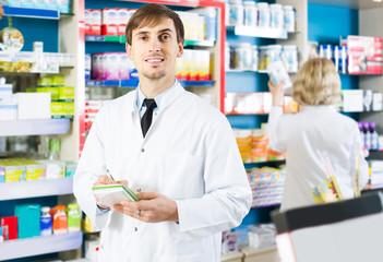 Portrait of male pharmacists working in modern farmacy