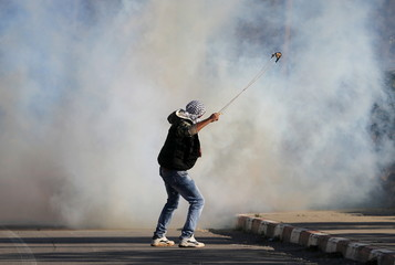 Palestinian protester uses a sling to hurl stones towards Israeli troops during clashes in Aboud village, near the West Bank city of Ramallah