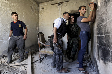 Members of the Free Syrian use a video camera to record the scene outside, in the old city of Aleppo