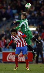 Atletico Madrid's Falcao gets challenged by Real Betis'  Ruben Perez during their King's Cup quarter-final first leg match at Vicente Calderon stadium in Madrid
