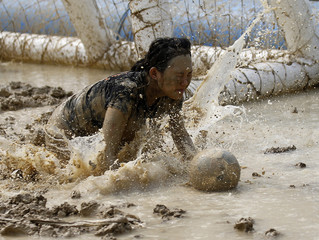 Female goalkeeper chases a ball during a match at the swamp soccer China tournament in Beijing