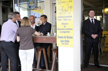 France's President Nicolas Sarkozy drinks a coffee in a restaurant along the beach in Cap d'Agde