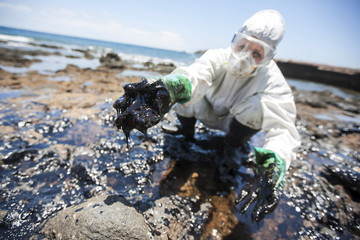 """A volunteer collects fuel oil from rocks at the """"Muelle Viejo"""" beach in Gran Canaria in Spain's Canary Islands"""