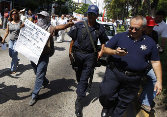 A teacher yells slogans at the chief of the municipal police Miguel Angel Albarran during a march in Acapulco