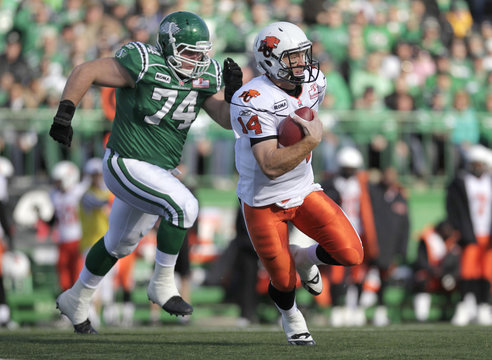 BC Lions quarterback Lulay runs up the ball while getting chased by Saskatchewan Roughriders defensive tackle Shologan during first half of their CFL football game in Regina