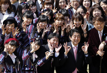 Japan's PM Abe poses with entertainment celebrities including members of girls' pop group HKT48, led by Sashihara, at a cherry blossom viewing party at Tokyo's Shinjuku Gyoen park