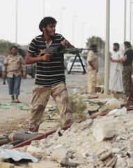 An anti-Gaddafi fighter returns fire during clashes with pro-Gaddafi forces in Sirte