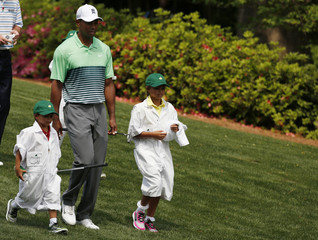 U.S. golfer Tiger Woods walks down the fairway with his children Sam and Charlie during the par 3 event held ahead of the 2015 Masters at Augusta National Golf Course in Augusta