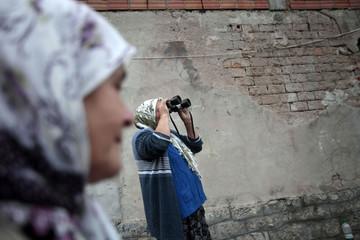 Kadric looks through a binoculars to watch over sheep next to her cousin Beguna in village Gladovici near Srebrenica