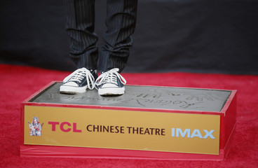 Director Roland Emmerich presses his feet into the cement during his Hand and Foot Print Ceremony in Hollywood