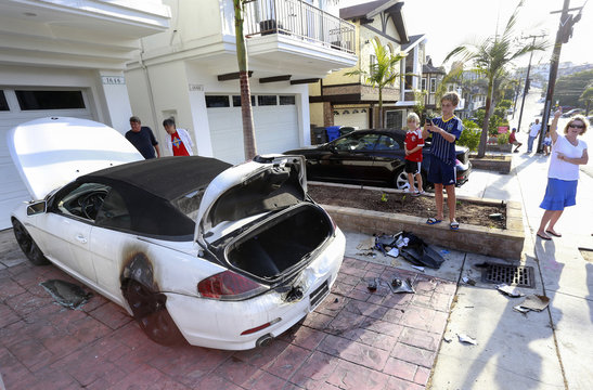 People look at a BMW car that was damaged by a lightning strike on Haynes Lane in a residential area of Redondo Beach