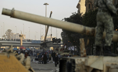 Egyptian army move burnt out vehicles as they help to clean up Tahrir Square in Cairo