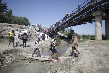 Haitians cross a river next to a collapsed bridge in the outskirts of Port-au-Prince