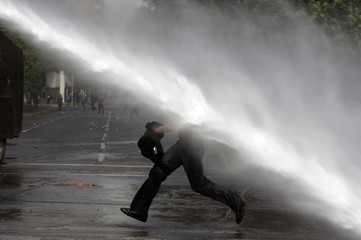 Demonstrators are hit by a jet of water released from a riot police vehicle during a rally against the public state education system in Santiago