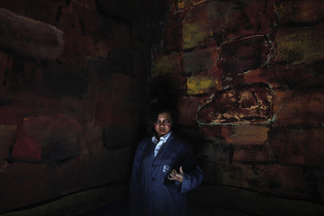 """A woman dressed as a ghost servant poses inside a tomb setting as part of the """"5D haunted house"""" at Hong Kong Ocean Park"""