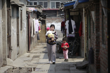 A woman carrying her child walks past houses with her daughter in a residential area for migrant workers in Beijing