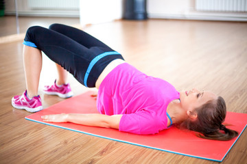 Happy woman doing pelvic muscle exercise on mat