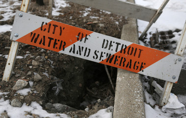 A City of Detroit Water and Sewerage safety barricade covers a hole along Jefferson Avenue in the Delray neighborhood of Detroit