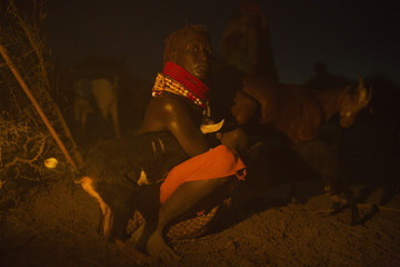 A Turkana woman poses for a photograph as she milks her goats the end of the day in her family's cattle kraal in the disputed area of the Ilemi triangle